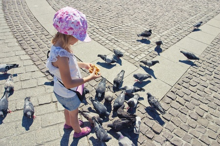 8 10 years: Little girl feeding pigeons on the square