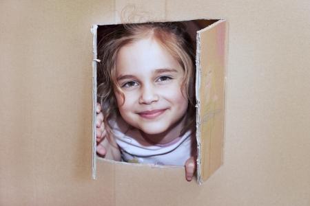 Little girl inside cardboard playhouse Stock Photo
