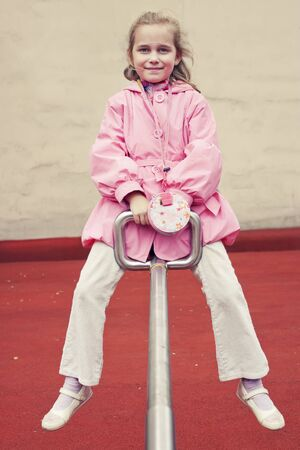 Little girl on a seesaw in the park Stock Photo