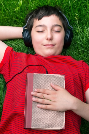 audio book: Boy is lying on a grass and he is listening audio book