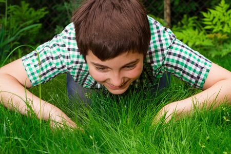 Boy looking for life in grass, in forest