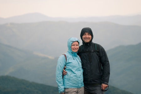 Happy couple at cold day on mountain trail