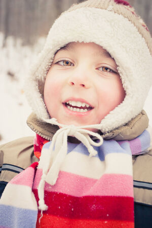 Boy dressed in cap and scarf at cold winter day Stock Photo
