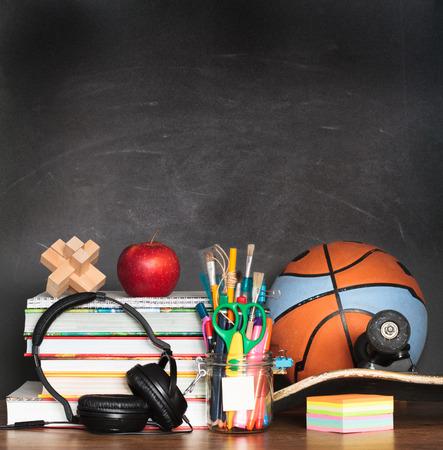 school desk: School accessories on desktop with blank blackboard in the background