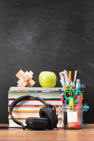 School accessories on desktop with blank blackboard in the background