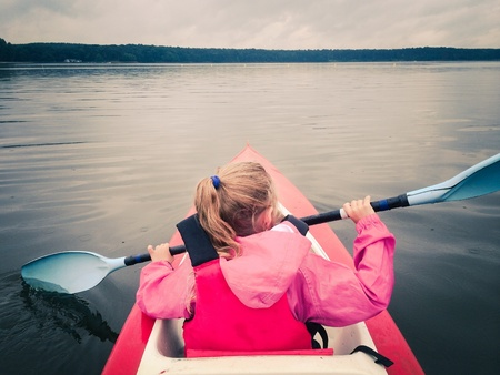 Little girl in kayak on a lake Reklamní fotografie - 31613042