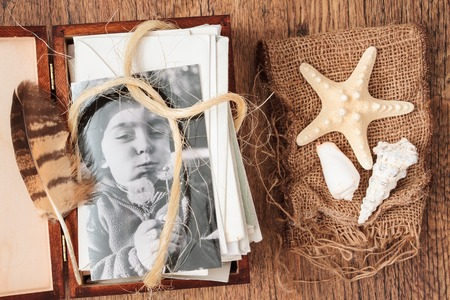 memento: Memories hidden in letters and photos. Shells and feather as mementos Stock Photo