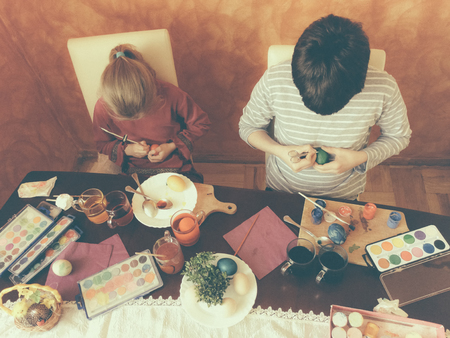 eternal life: Brother and sister painting Easter eggs at home Stock Photo