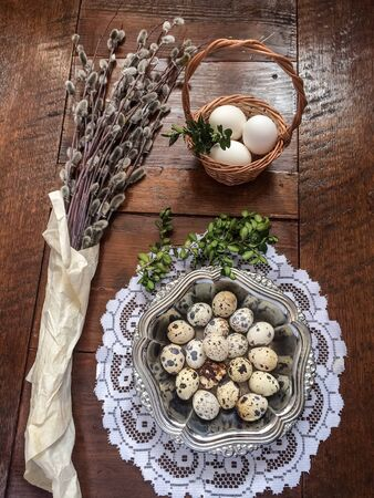 metal: Easter composition of willow twigs with catkins, boxwood, quail eggs in a metal dish, easter basket with eggs, set on old wooden table. Catkins are wrapped up in paper. There is lacy napkin under the dish