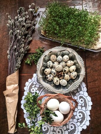 metal: Easter composition of willow twigs with catkins, boxwood, quail eggs in a metal dish, easter basket with eggs and cress, set on old wooden table. Catkins are wrapped up in paper. There is lacy napkin under the basket Stock Photo