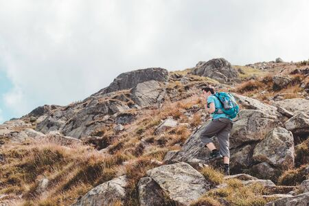 Teenager hiking alone in the mountains Stock Photo