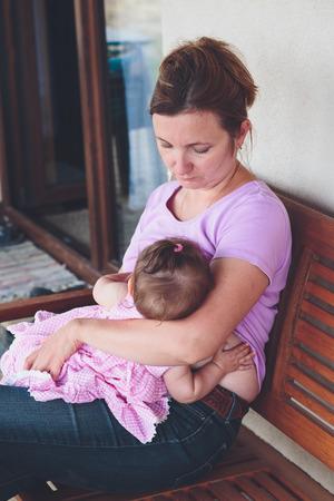 amamantando: Primer plano de la madre que amamanta a su peque�o beb� en el patio Foto de archivo