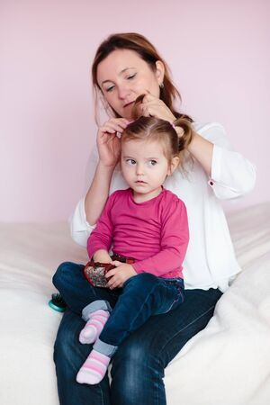 Mother doing her little daughters hair Stock Photo