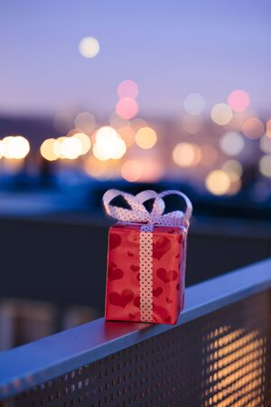 Christmas gift left on railing of balcony with blurred lights in the background