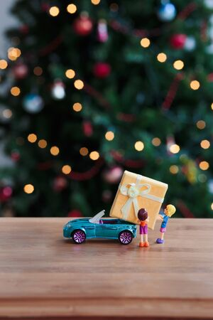 Toy figures packing big Christmas gift into the car Stock Photo