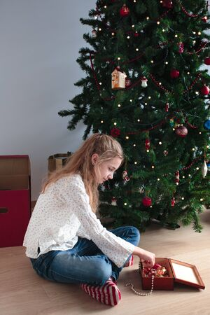 decorating: Young girl decorating Christmas tree at home Stock Photo