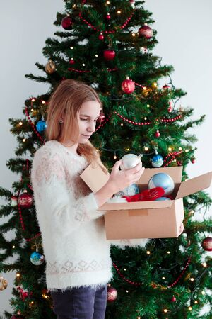 decorate: Young girl decorating Christmas tree at home Stock Photo