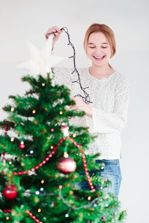 decorate: Young girl decorating Christmas tree with lights at home