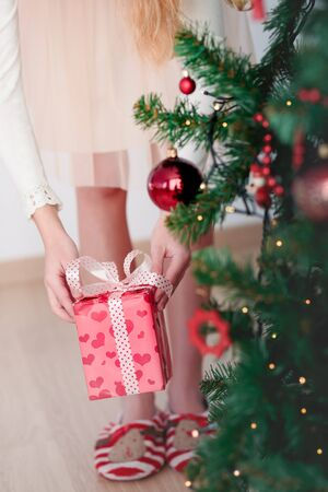 Closeup of girl getting Christmas gift from under a tree