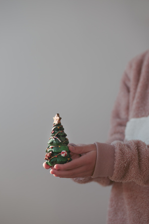 holiday tradition: Girl wearing warm sweater holding Christmas tree figurine