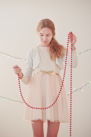 Portrait of young girl unwrapping red Christmas decorations Stock Photo