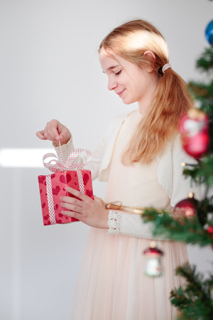 Happy girl unpacking Christmas gift standing behind a tree Stock Photo