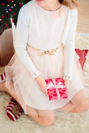 Top shot of girl wearing dress holding Christmas gift and sitting on a carpet