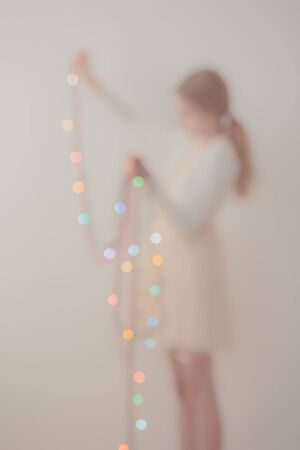 Out of focus portrait of young girl unwrapping colorful Christmas lights