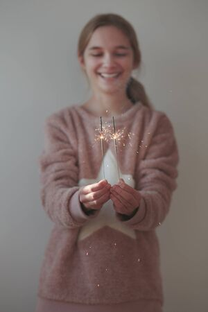 Young smiling girl holding sparklers