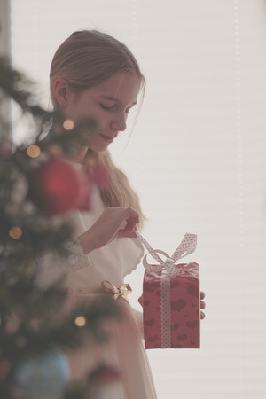 Girl unpacking Christmas gift standing behind a tree Stock Photo