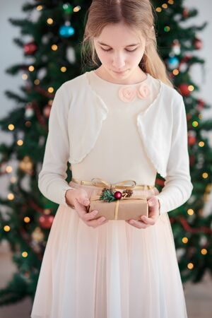 Girl wearing pink dress holding Christmas gift and standing in front of Christmas tree Stock Photo