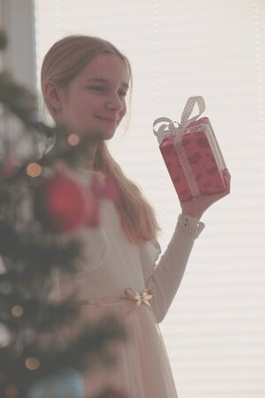 Happy smiling girl holding Christmas gift standing behinde a tree