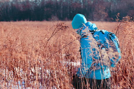 Boy hiking through meadows in the wintertime Stock Photo
