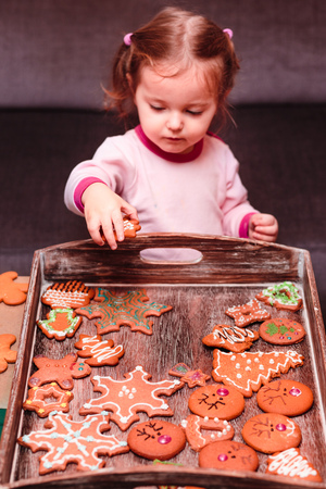 Little girl placing Christmas gingerbread cookies on wooden tray