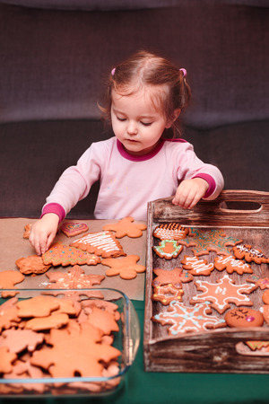 decoracion mesas: Little girl placing Christmas gingerbread cookies on wooden tray