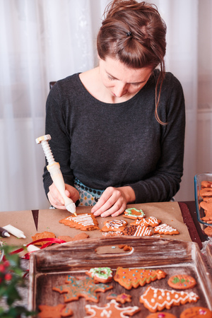 Woman decorating baked Christmas gingerbread cookies with frosting Stock Photo
