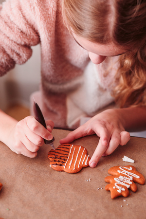 Girl decorating baked Christmas gingerbread cookies with chocolate writing pen Stock Photo