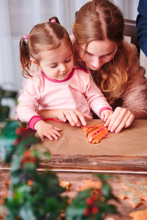 Girls tying baked Christmas gingerbread cookies with ribbon Stock Photo