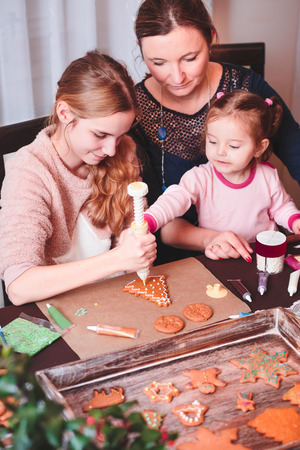 Family decorating baked Christmas gingerbread cookies with frosting