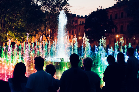 People looking at fountain and lights in the evening in the city centre