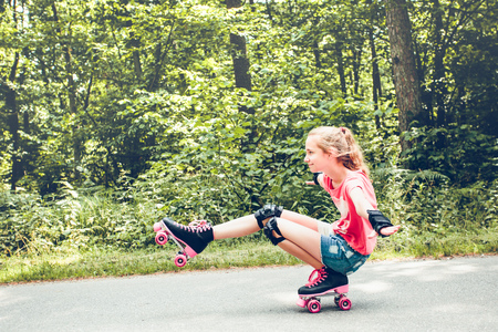 Young girl roller skating down on a forest road on summer day