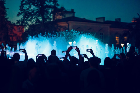 People taking photos of fountain and lights with smartphones in the evening in the city centre