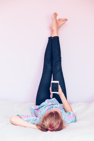 Young gril using mobile phone lying in bed with legs up