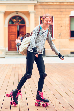 Young girl roller skating in a town spending time actively outdoors on summer day