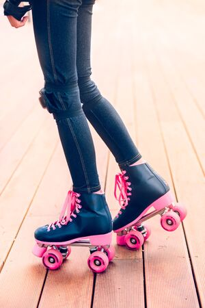 Legs of young girl wearing jeans and skates standing on wooden stage