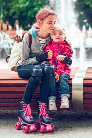 Young girl hugging her little sister while sitting on bench in a city centre