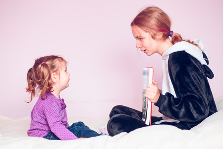 Girl showing the pictures in a book her younger sister while sitting on bed