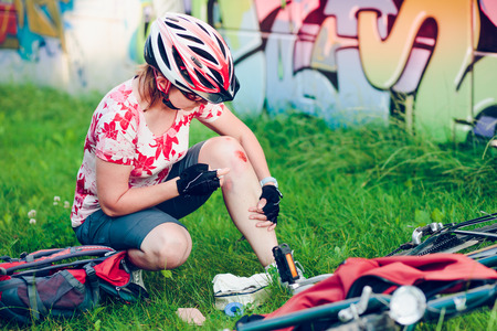 Woman dressing the wound on her knee with medicine in spray and gauze on bike trip on summer day