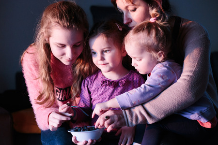 Family, mother with three daughters, teenage girl , kid and toddler, enjoying eating fresh blueberries from small bowl together at home Reklamní fotografie - 123622649