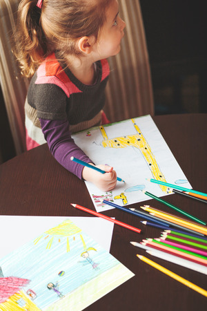 Little girl drawing a colorful pictures of giraffe and playing children using pencil crayons sitting at table indoors. Shot from above
